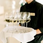 Server holding glasses of white wine